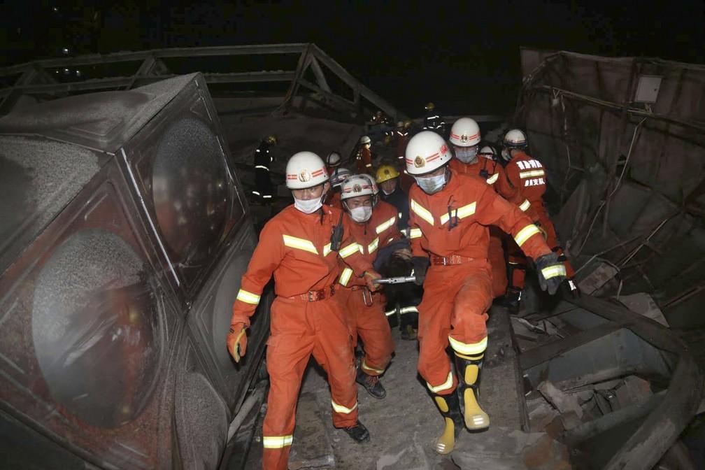 Equipe faz resgate de vítimas do desabamento de hotel com pessoas em quarentena por coronavírus na China — Foto: Chinatopix Via AP