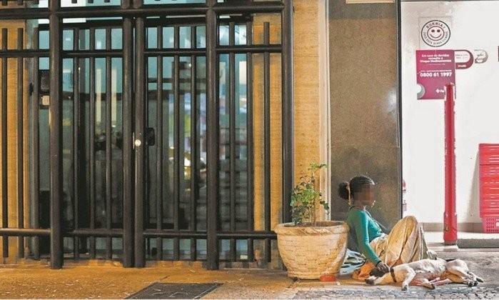 Mulher se abriga próximo à portaria de um prédio