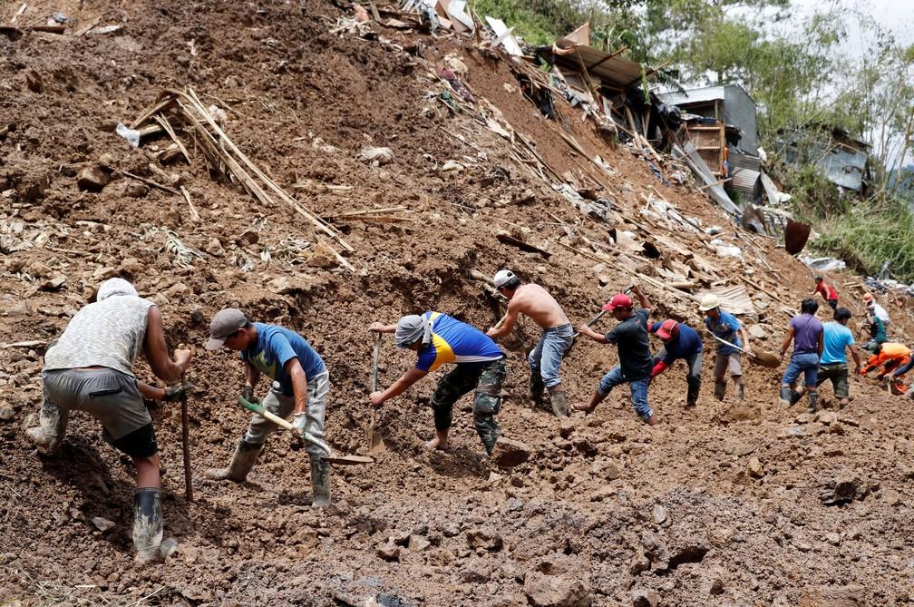 Socorristas trabalham nesta segunda-feira (17) em mina soterrada durante busca por mineiros que ficaram presos no local após a passagem do tufão Mangkhut — Foto: Erik De Castro/Reuters