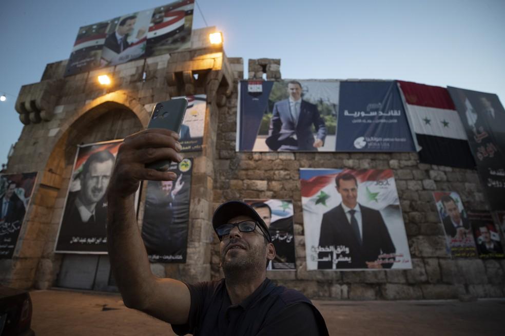 Sírio faz selfie com cartazes de Bashar Al-Assad na capital do país, Damasco, antes da eleição presidencial, na quarta (25) — Foto: Hassan Ammar/AP