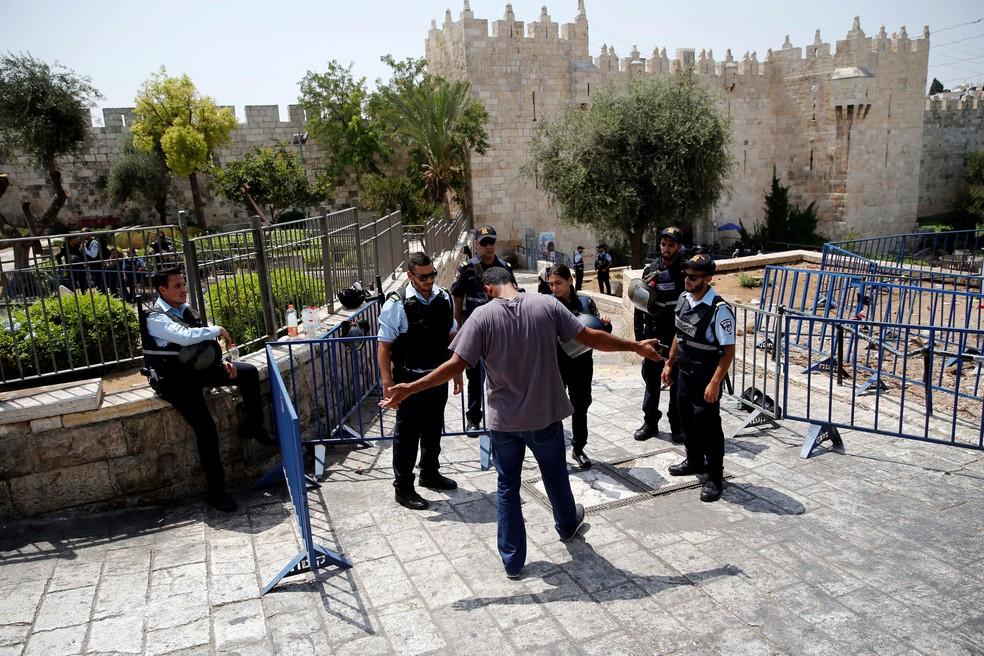 Polícia israelense para palestino para inspeção na Porta de Damasco, entrada da cidade velha de Jerusalém, nesta sexta-feira (21)  (Foto: Amir Cohen/ Reuters)