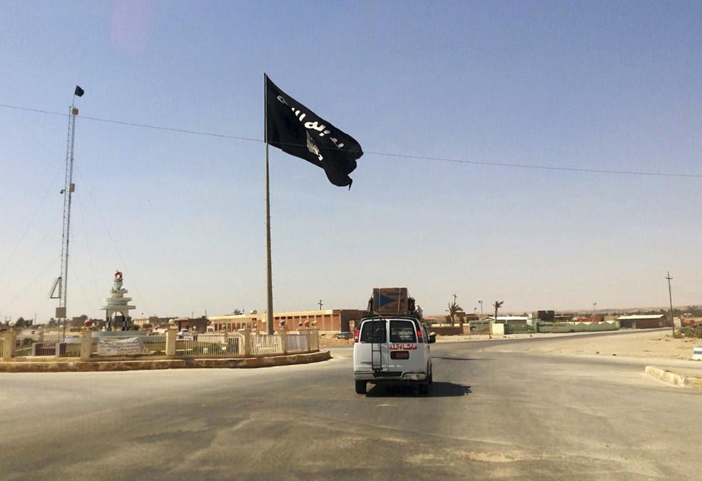 Imagem de julho de 2014 mostra bandeira do Estado Islâmico estendida sobre Rawa, recapturada pela coalizão, segundo o Iraque (Foto: AP Photo)