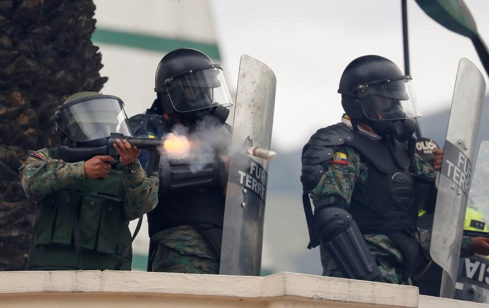 Policial dispara durante protesto em Quito nesta terça (8) — Foto: Reuters/Carlos Garcia Rawlins