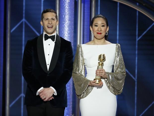 Os apresentadores da noite Andy Samberg e Sandra Oh, segurando seu prêmio de Melhor Atriz em Série de Drama  (Foto: Getty Images)