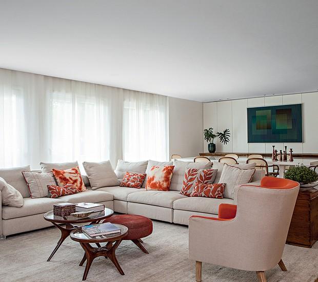 O estar neutro abre-se a pitadas de laranja, seja nas almofadas sobre o sofá italiano, seja no tecido da poltrona. A cor quente combina com o bege. Projeto da designer de interiores Renata Paula (Foto: Lufe Gomes/Casa e Jardim)