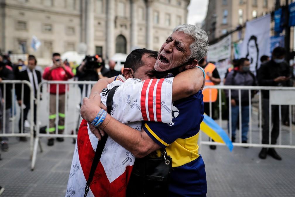 Torcedores do River Plate e do Boca Juniors se abraçam chorando durante velório de Maradona em Buenos Aires — Foto:  EFE/Juan Ignacio Roncoroni