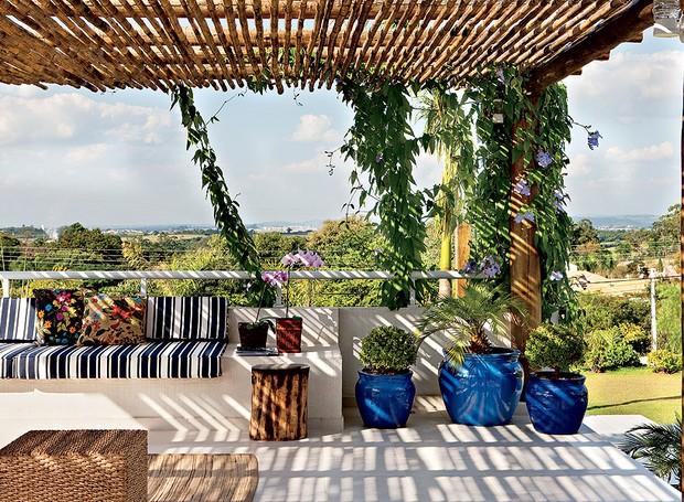 Sobre a laje da garagem, a arquiteta Lígia Resston criou o terraço com cobertura de bambu e estrutura de toras de eucalipito, nas quais cresce a trepadeira tumbérgia (Foto: Edu Castello/Casa e Jardim)