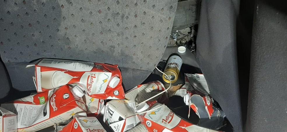 Caixas de leite e lata de cerveja no carro — Foto: José Aparecido/TV Morena