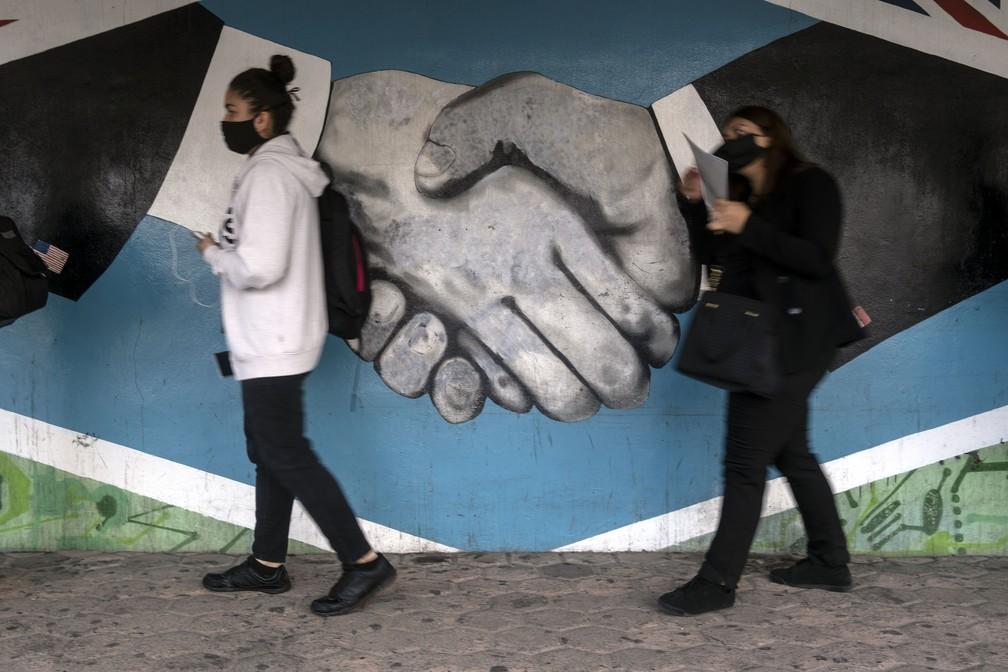 Com máscaras, pessoas autorizadas cruzam a fronteira entre o México e os EUA em Tijuana em 7 de julho — Foto: Guillermo Arias/AFP