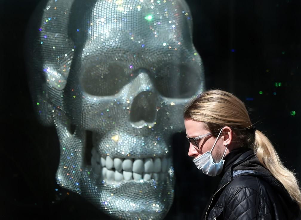 Homem usando máscara protetora contra a Covid-19 passa em frente a uma loja decorada com uma caveira em Kiev, na Ucrânia, nesta quinta-feira (9). — Foto: Sergei Supinsky / AFP