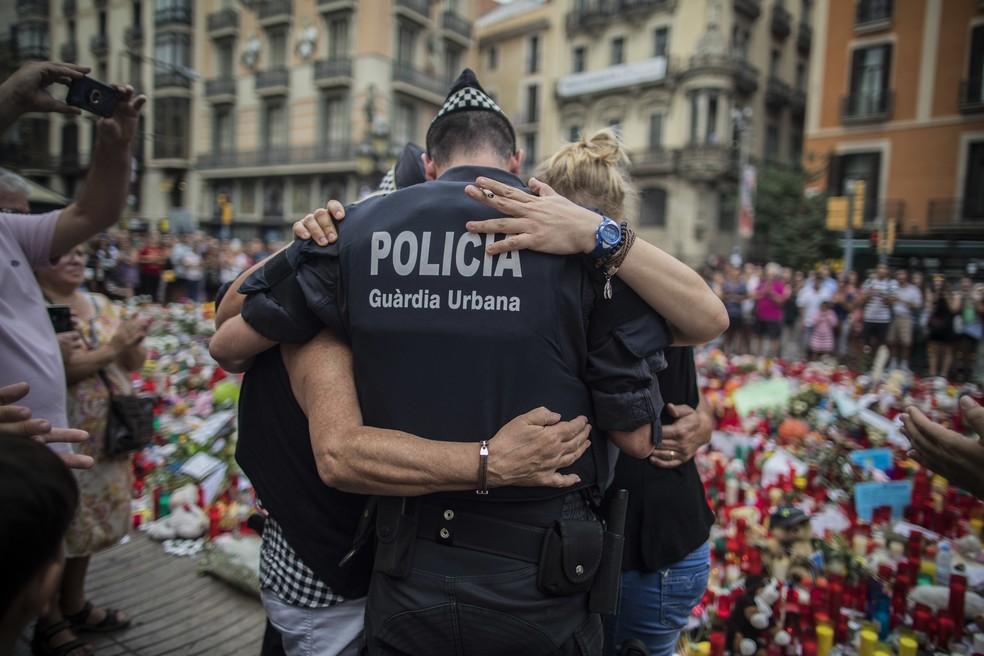 Policial abraça família em frente ao memorial em memória das vítimas do ataque em Las Ramblas, em Barcelona (Foto: Santi Palacios / AP Photo)