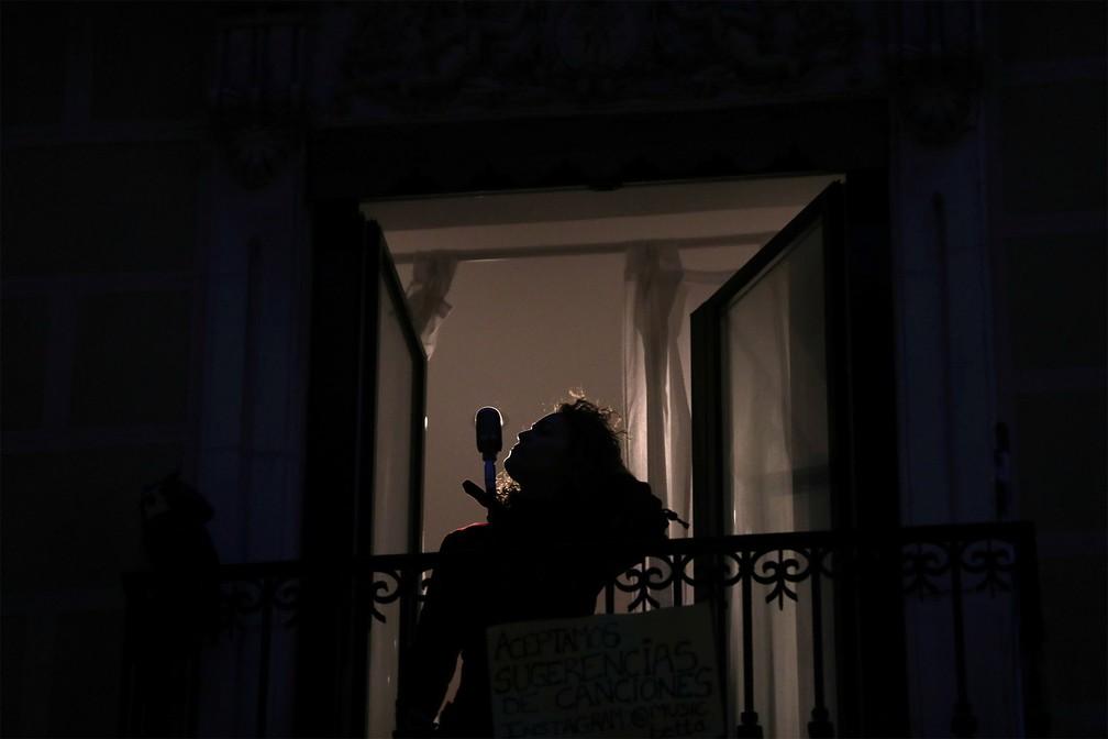 19 de março - A cantora espanhola de blues Beatriz Berodia 'Betta' canta de uma varanda durante uma das apresentações diárias para homenagear os trabalhadores da área da saúde em tempos de coronavírus e para alegrar a vida em quarentena da vizinhança, em um bairro de Madri, na Espanha — Foto: Susana Vera/Reuters
