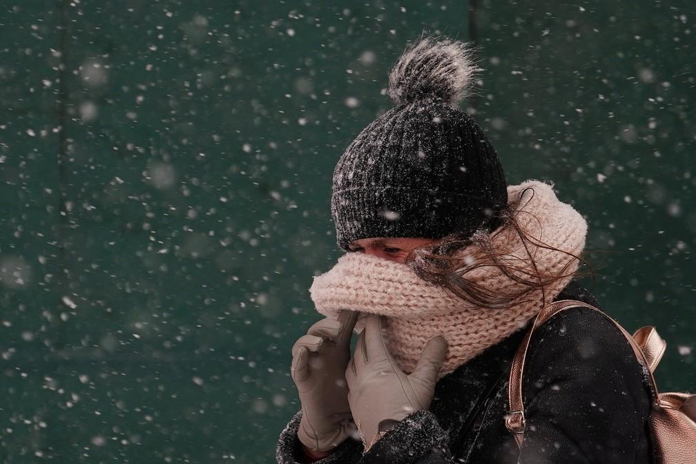 4 de janeiro - Mulher cobre o rosto enquanto caminha pela Times Square durante tempestade de neve na cidade de Nova York, nos Estados Unidos (Foto: Carlo Allegri/Reuters)