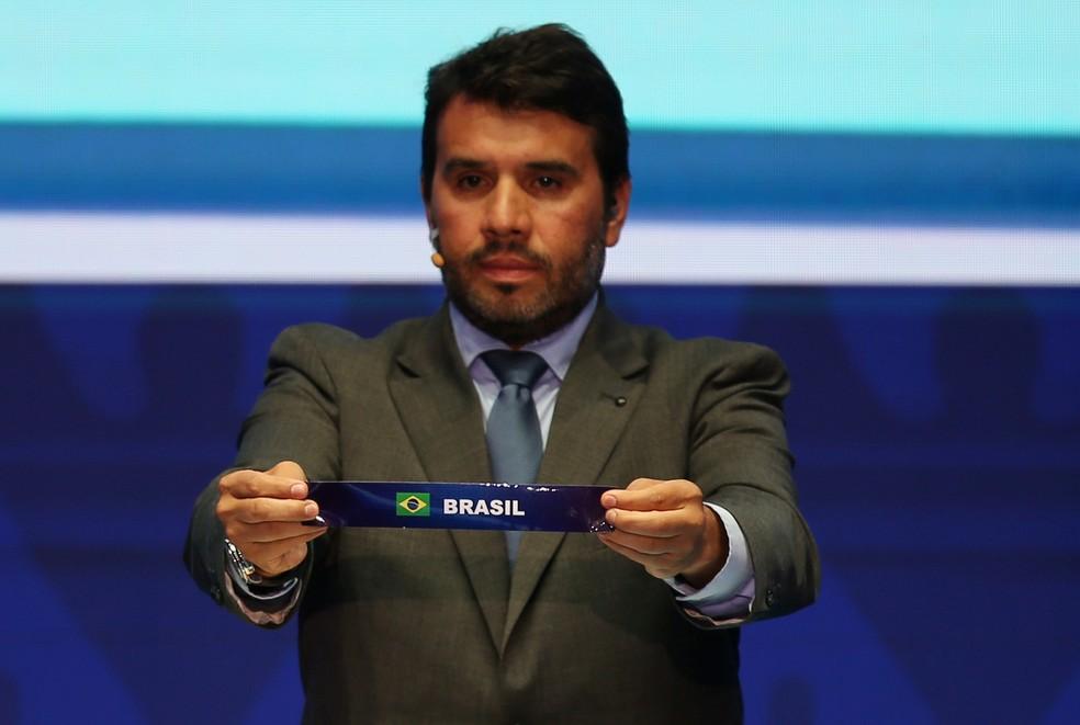 Diretor de Competições de Seleções da Conmebol, Hugo Figueredo, mostra o nome do Brasil no sorteio — Foto: Luisa González/Reuters