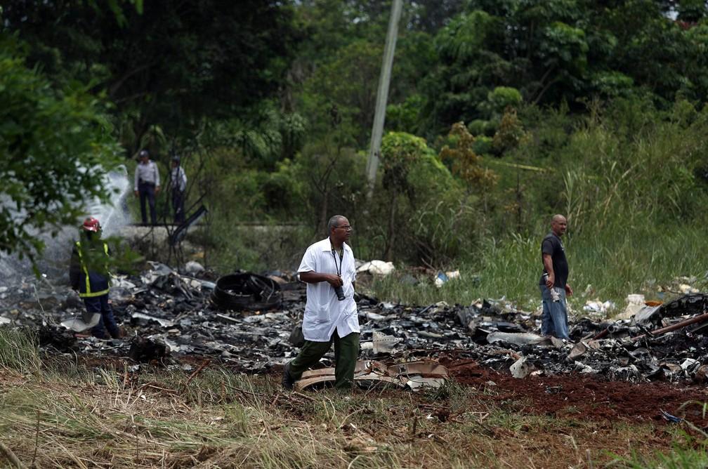 Fotógrafo trabalha no local onde um avião com 113 pessoas a bordo caiu logo após decolagem em Havana, Cuba (Foto: Alexandre Meneghini/Reuters)