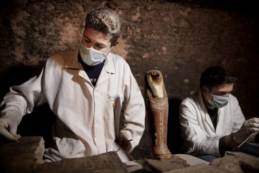 Arqueologistas recuperam uma estátua dentro da tumba encontrada perto de Sacará — Foto: Nariman El-Mofty/AP