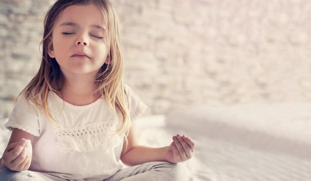 Menina meditando no quarto (Foto: Thinkstock)