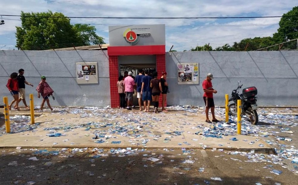 Santinhos espalhados o chão em frente ao Centro Educacional 1 de Planaltina, no DF — Foto: Letícia Carvalho/G1