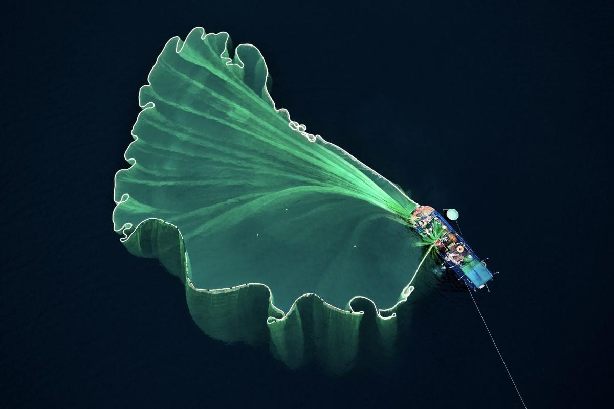 O segundo lugar foi para a imagem que registra o exato momento em que um pescador joga a rede na água (Foto: Trung Pham/International Drone Competition)