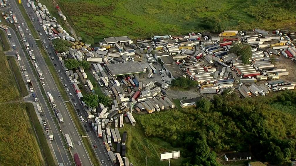 Dezenas de caminhões parados no acostamento e em um posto em Seropédica (Foto: Reprodução/TV Globo)