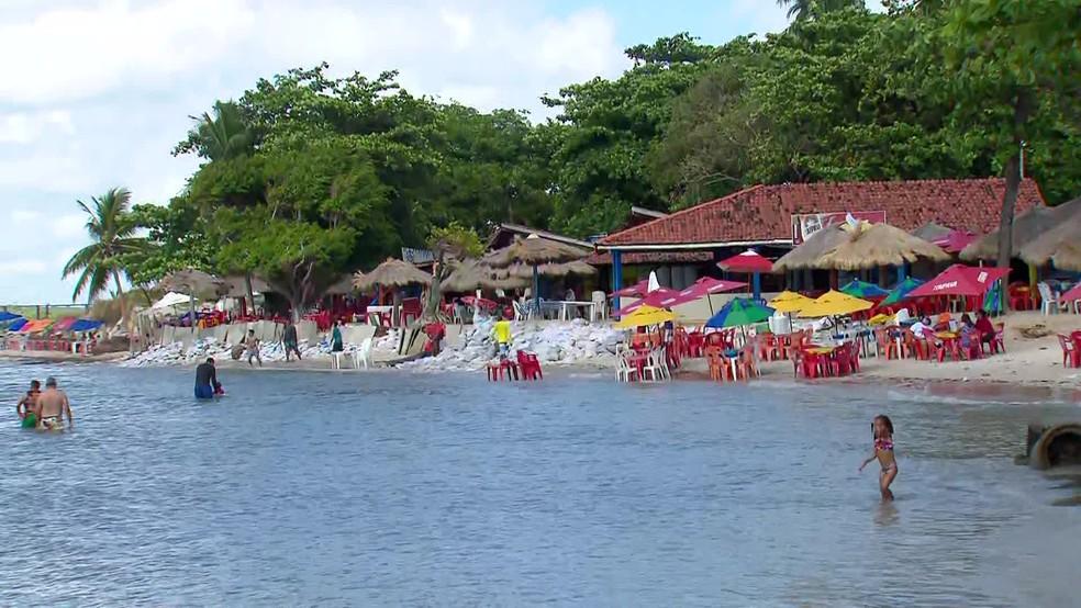 Bares perto do Forte Orange colocaram sacas de areia para tentar conter o mar — Foto: Reprodução/TV Globo