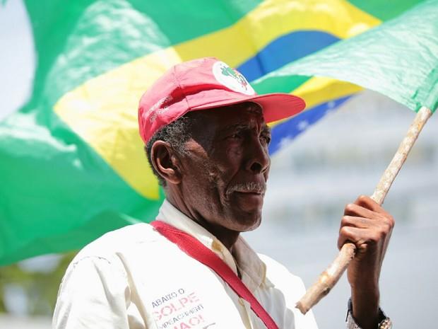 Homem com boné de movimento agrário agita bandeira do Brasil duranrte manifestação pró-Dilma em Maceió (Foto: Jonathan Lins/G1)