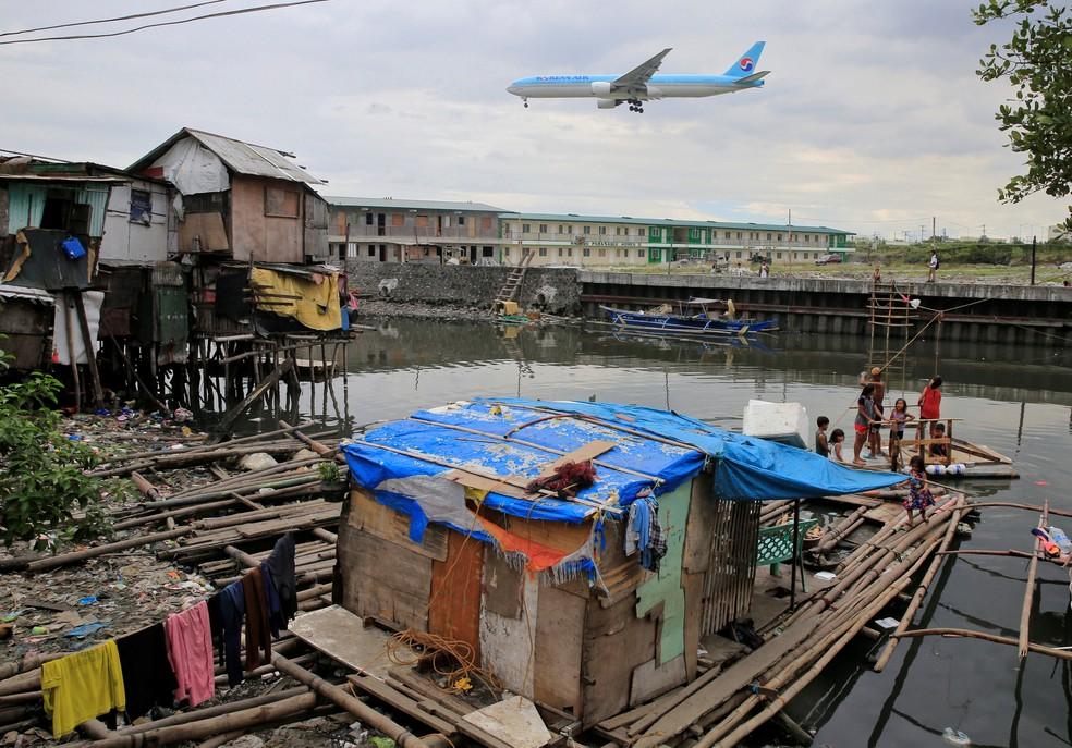 Avião sobrevoa casa de palafitas na cidade Paranaque, nas Filipinas, em foto de 11 de janeiro  (Foto: Romeo Ranoco/ Reuters)