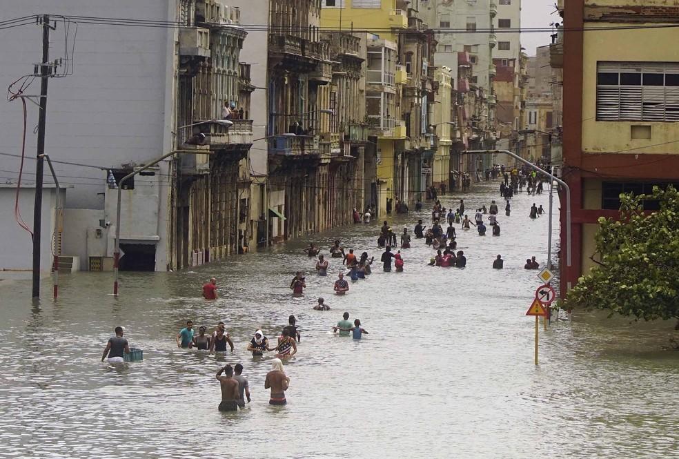 Pessoas atravessam ruas inundadas em Havana após a passagem do furacão Irma, em Cuba (Foto: Ramon Espinosa/AP)