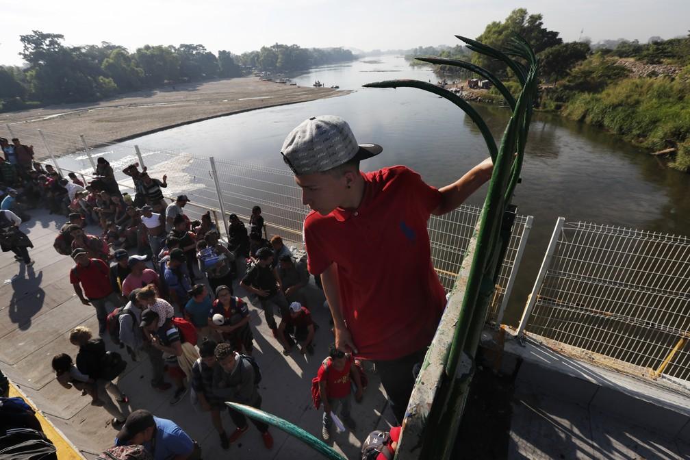 Migrante de caravana escala grade neste sábado (18) para tentar entrar no México pela fronteira com a Guatemala e seguir rumo aos EUA — Foto: Marco Ugarte/AP Photo