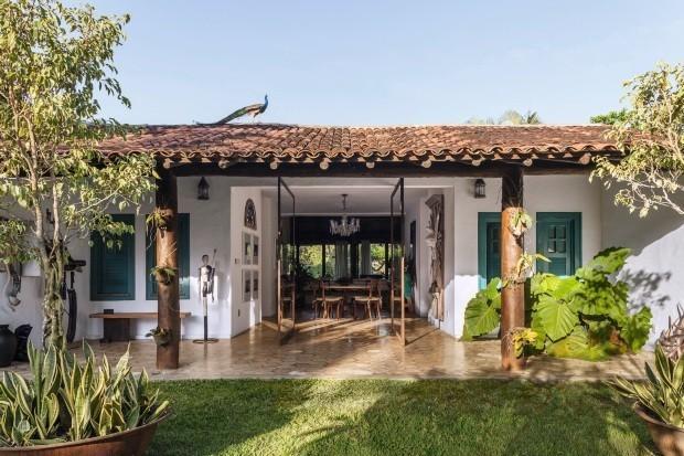 Branca e com janelas pintadas de azul, a casa avarandada ganhou portas pivotantes de vidro e aço corten para integrar melhor o interior e o exterior (Foto: Victor Affaro / Casa e Jardim)