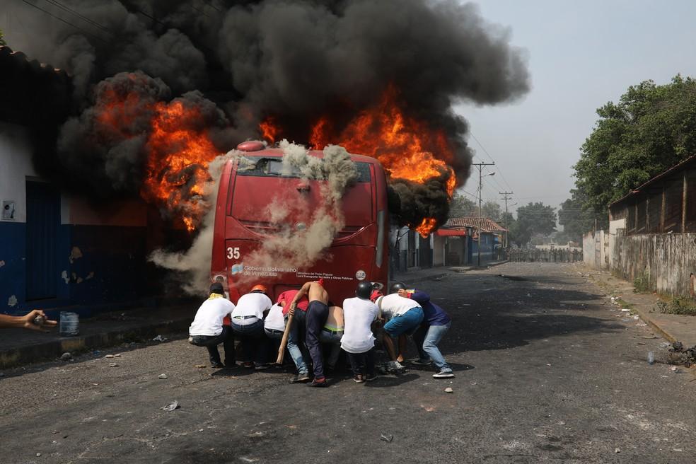 Manifestantes empurram um ônibus que foi incendiado durante confrontos com a Guarda Nacional Bolivariana em Ureña — Foto: Rodrigo Abd/AP
