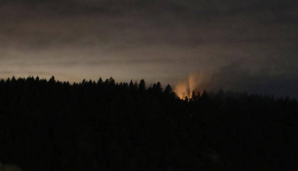 Imagem de longa exposição mostra fumaça e luz alaranjada na ilha de Ketron, em Washington, após queda de avião (Foto: Ted S. Warren/AP Photo)