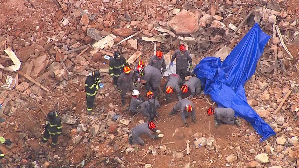 Bombeiros fazem escavação manual após identificarem corpo em escombros (Foto: Reprodução/TV Globo)