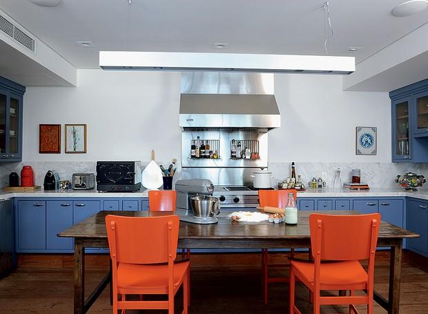 """A madeira de demolição no piso e as cores alegres nos móveis reforçam a ideia de que a cozinha é um espaço também para receber neste apartamento. """"Os tons de azul e laranja deram jovialidade ao espaço"""", diz a designer de interiores Marina Linhares (Foto: Marcelo Magnani/Casa e Jardim)"""