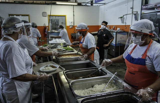 NITEROI, BRAZIL - AUGUST 05: Employees wearing face masks prepare food at a popular soup kitchen on August 5, 2020 in Niteroi, Brazil. Employees received special training to ensure the safety of visitors. The site will intensify the cleaning process and w (Foto: Getty Images)