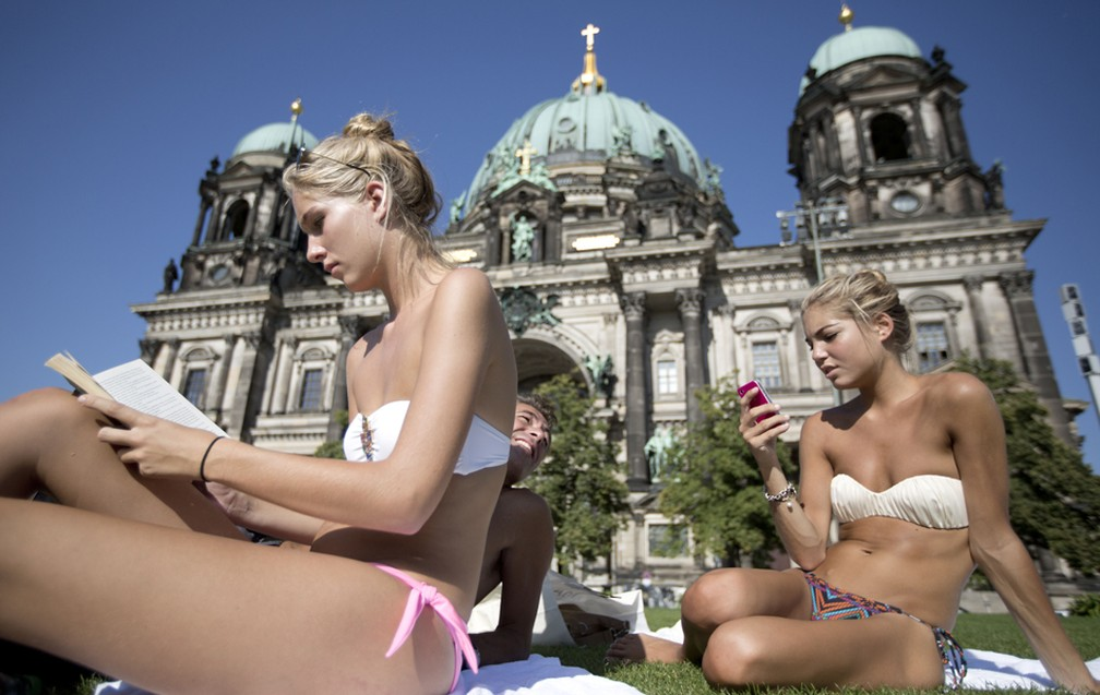 Turistas toman sol em frente a Catedral de Berlim, nesta domingo (19). Em alguns lugares da Alemanha, a temperatura chega a 39°C — Foto: AP Photo/Gero Breloer