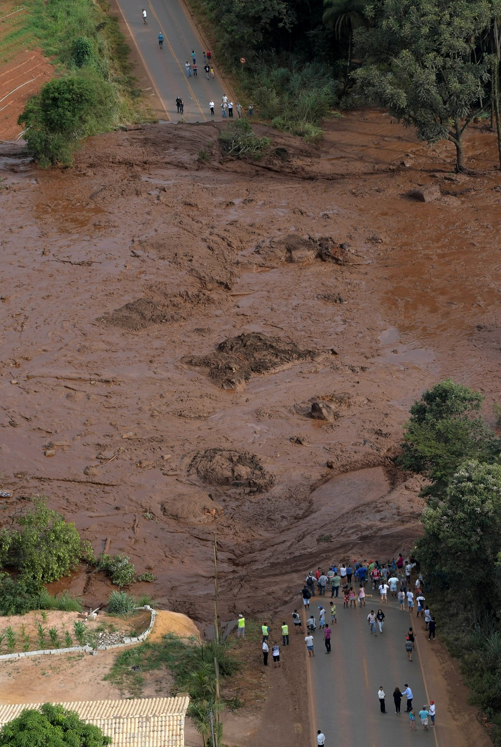 Moradores perto da lama que vazou da barragem em Brumadinho — Foto: Reuters/Washington Alves