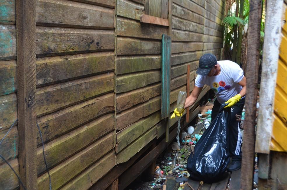 Voluntários limpam lixo no entorno de casas em Santana — Foto: Carlos Alberto Jr/G1