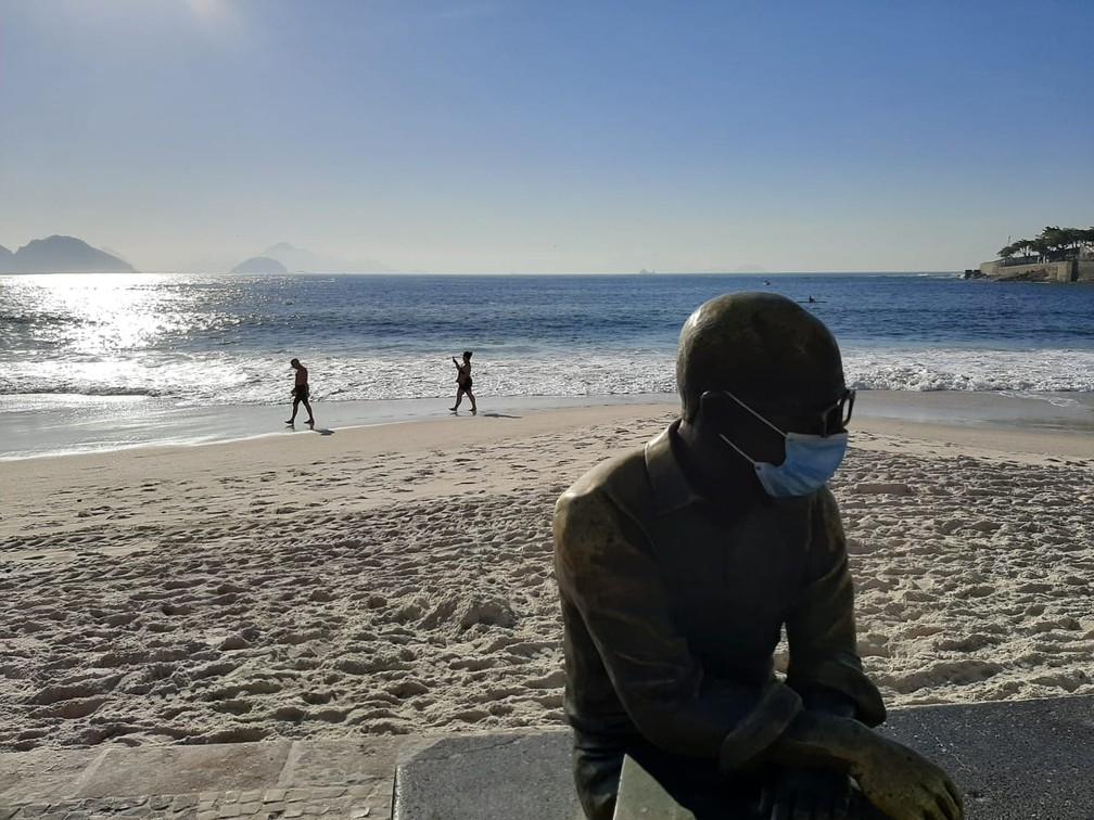 Cariocas caminham na Praia de Copacabana, em frente à Estátua de Drummond — Foto: Daniel Silveira/G1