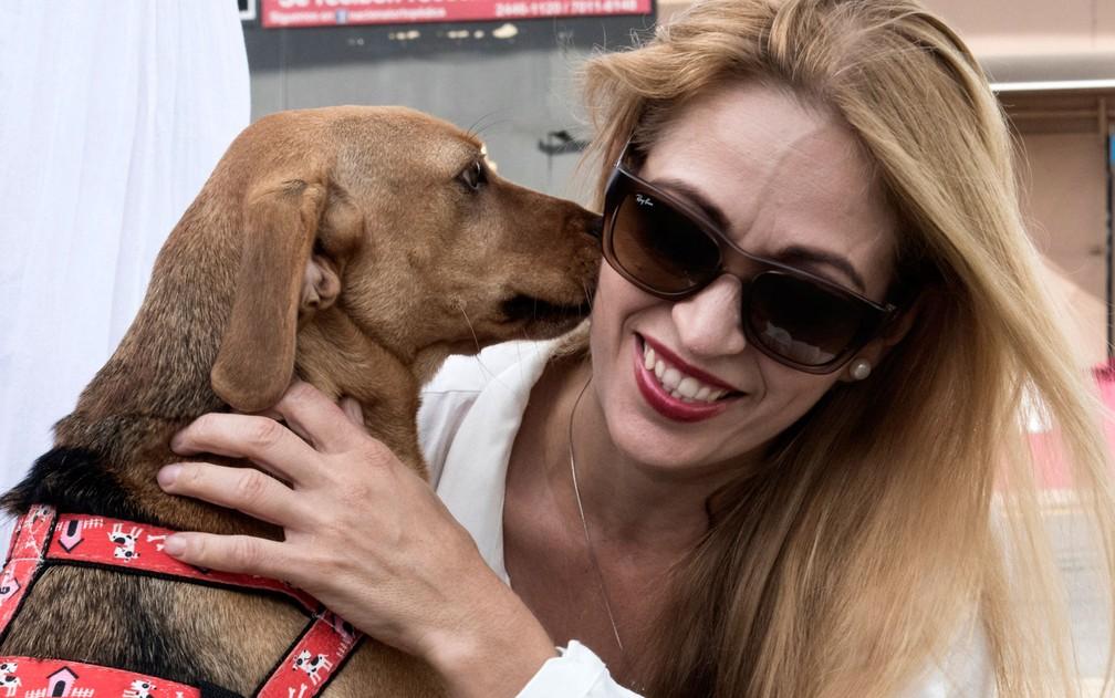 Campeão 'beija' sua atual dona, Isabel Aguilar, do lado de fora da corte em Atenas, na Costa Rica, na segunda-feira (22) — Foto: Ezequiel Becerra/AFP