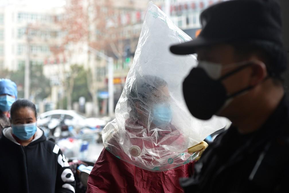 Um morador de Wuhan caminha em frente a um supermercado com máscara e sacola plástica em meio a surto de coronavírus — Foto: STR/AFP