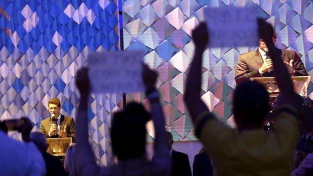 Em evento em Salvador (BA), pessoas na plateia protestam durante fala de Salles; ministro atribuiu aumento de incêndios ao clima (Foto: EPA/BBC)