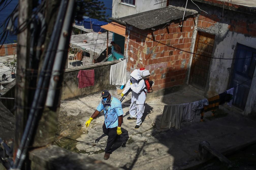 24 de abril: agentes de limpeza desinfectam a Favela do Vidigal, no Rio de Janeiro. — Foto: Pilar Olivares/Reuters