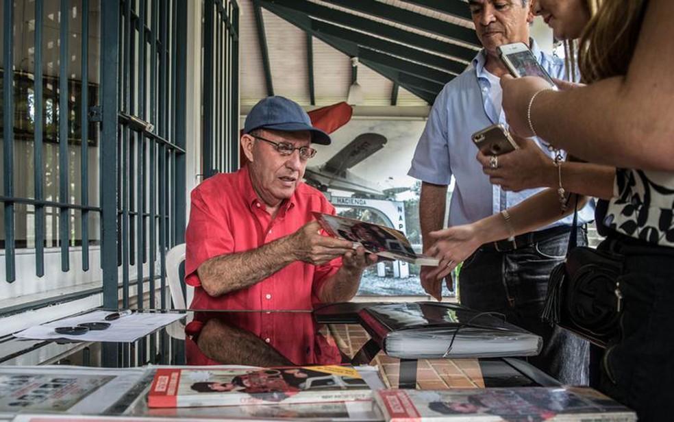 Roberto Escobar conta a turistas a sua versão da verdade e autografa fotos do irmão (Foto: DW/A. Williams)
