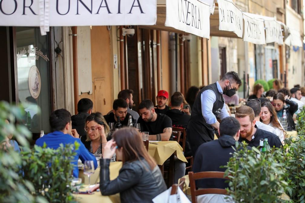 Pessoas almoçam ao ar livre em restaurante em Roma, na Itália, em 26 de abril de 2021, com grande parte do país voltando à 'zona amarela' e amenizando as restrições para frear a pandemia do novo coronavírus (Covid-19) — Foto: Yara Nardi/Reuters