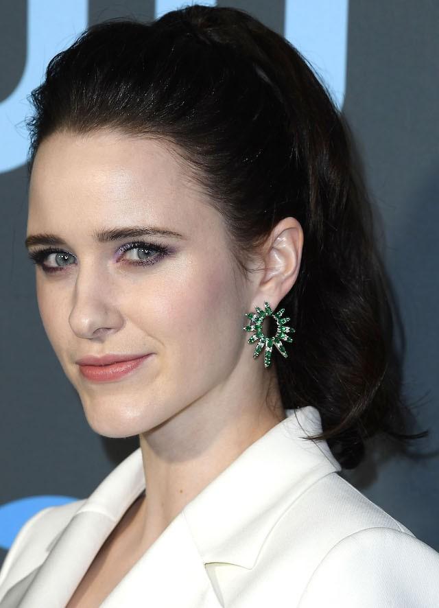 Rachel Brosnahan acertou ao contrastar o brinco de esmeraldas com a sombra lilás, arrematando o visual com um rabo alto bem volumoso com topete sessentinha. (Foto: Getty Images)