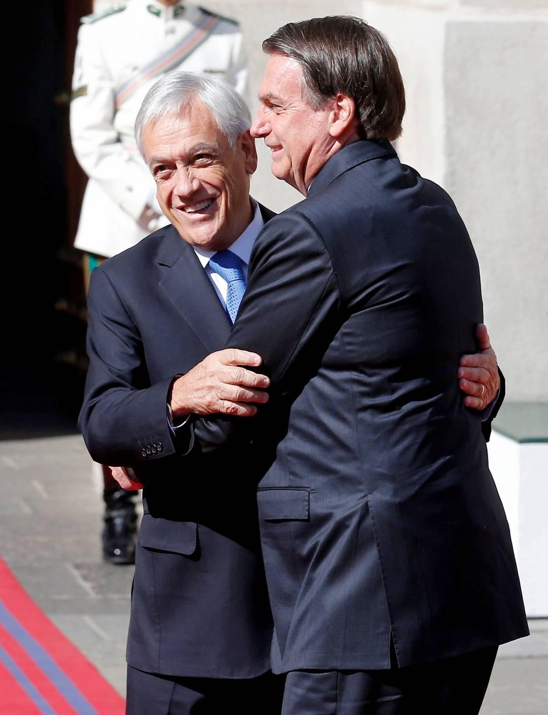 Presidente Jair Bolsonaro abraça president chileno Sebastián Piñera ao chegar ao palácio presidencial La Moneda, em Santiago, no Chile, nesta sexta-feira (22)