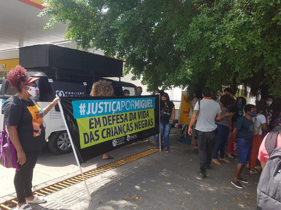 Representantes de movimentos sociais se reúnem e estendem faixas do lado de fora da vara onde ocorre a audiência do Caso Miguel — Foto: Katherine Coutinho/G1