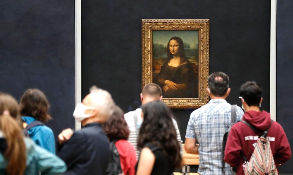 Visitantes usando máscaras tiram fotos em frente à Mona Lisa, obra-prima de Leonardo da Vinci, no Museu do Louvre em Paris, nesta segunda-feira (6)  — Foto: Francois Guillot / AFP