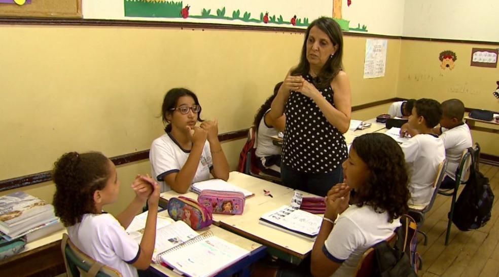 Por meio de sinais, alunas se entendem com a professora durante atividade em escola em Jaboticabal, SP (Foto: Carlos Trinca/EPTV)